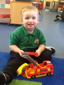 Nursery child playing with a fire engine