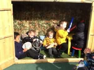 Nursery children playing in a shed