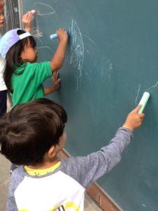 Nursery children drawing on a chalkboard